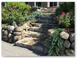 Boulder wall with garden and stamped concrete 01