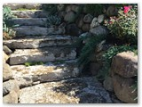 Boulder wall with garden and stamped concrete 02