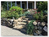 Boulder wall with garden and stamped concrete 03